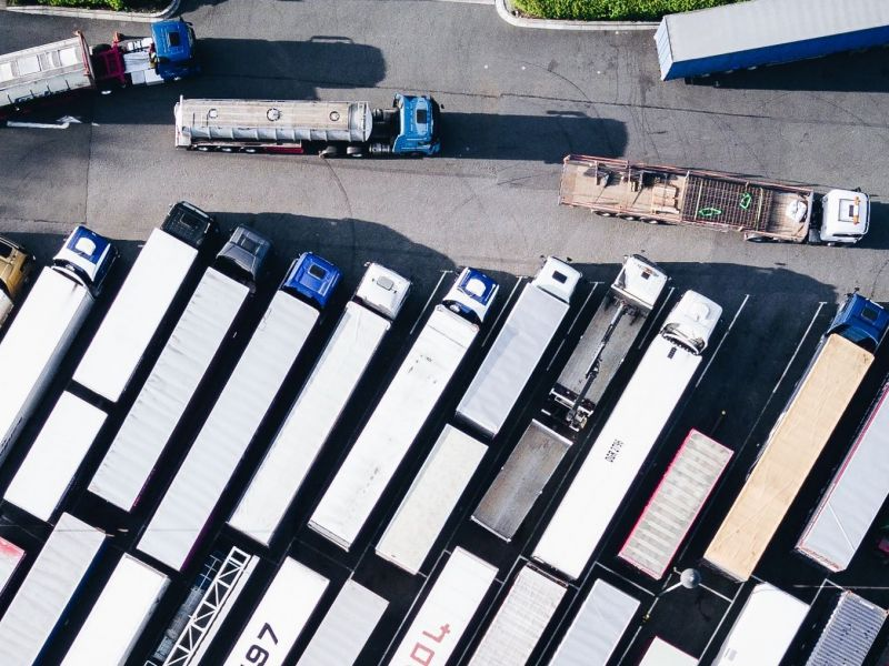 An overhead view of semi trucks arranged in rows in a parking lot.